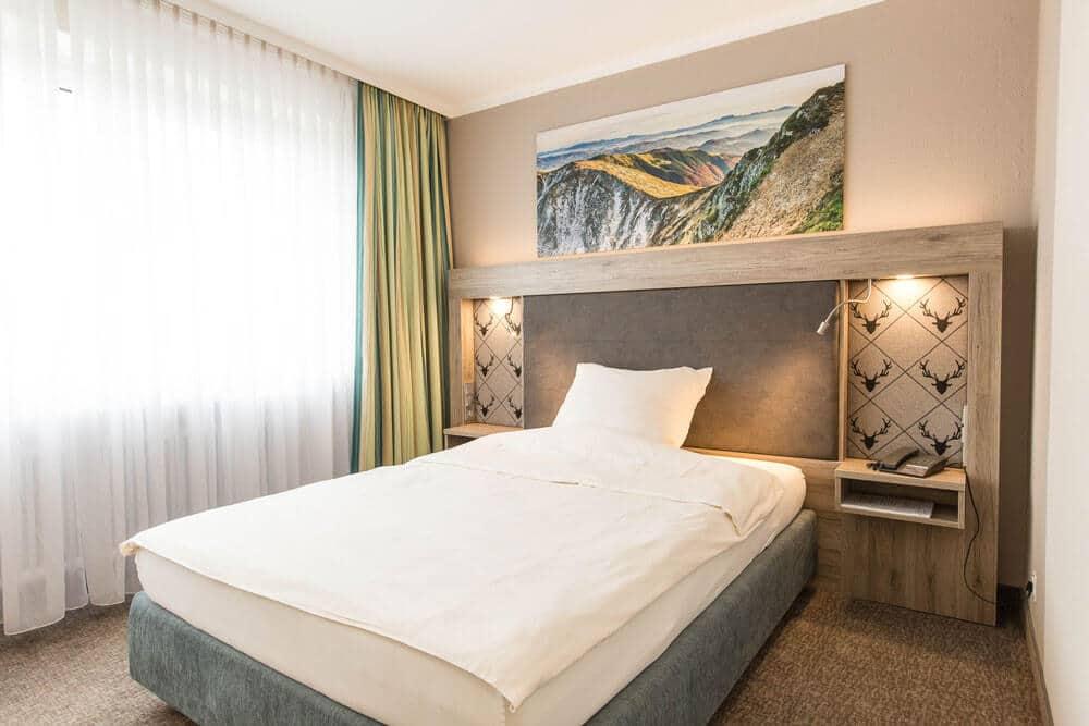 Bett mit Bergefoto, Premium-Zimmer, Hotel Bavaria Oldenburg